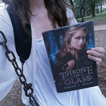Sitting on swing, holding Throne of Glass book