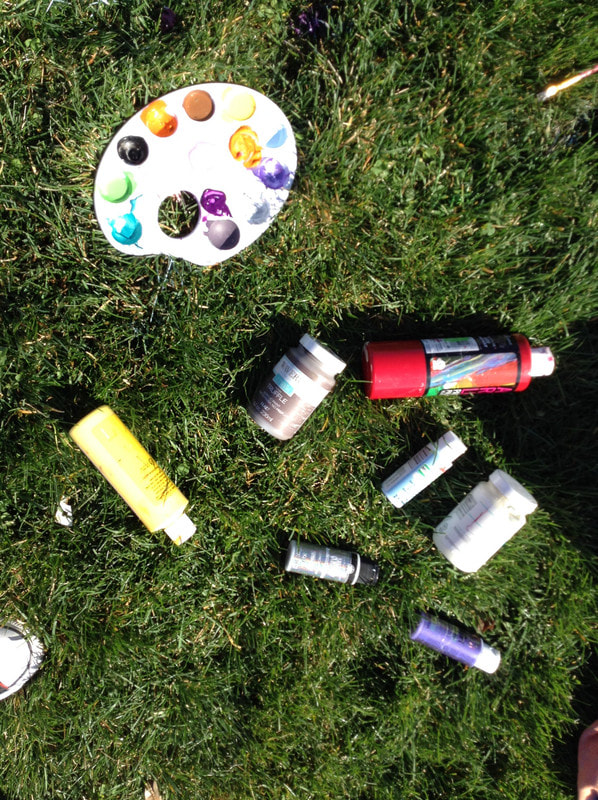 Bottles of paint and a palette on grass