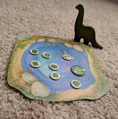 The watering hole from the board game Evolution with food pieces and the dinosaur player marker
