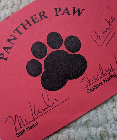 Black panther paw on red paper