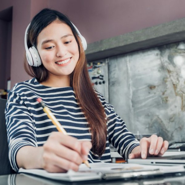Young lady smiling, wearing headphones, and writing with a pencil