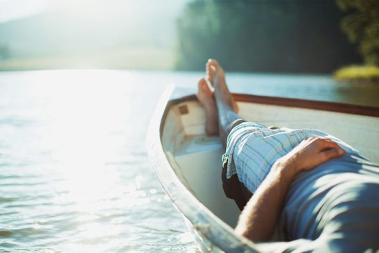 Barefoot man relaxing in rowboat